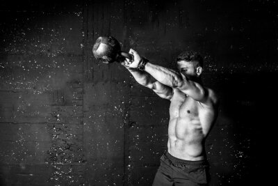 Sticker Young strong sweaty focused fit muscular man with big muscles holding heavy kettle bell for swing cross training hard core workout in the gym black and white