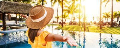 Sticker Young woman traveler relaxing and enjoying the sunset by a tropical resort pool while traveling for summer vacation
