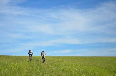 Zwei Biker Silhouette auf der Reise in der Natur mit immergrünen Bäumen und Wiese. Biker bewegen sich auf Horizont, der bunt ist und voller letzter Sonnenuntergang Licht