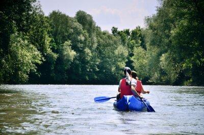 Zwei Freunde im Kanu schwimmen auf dem Fluss zwischen schönen grünen Wald