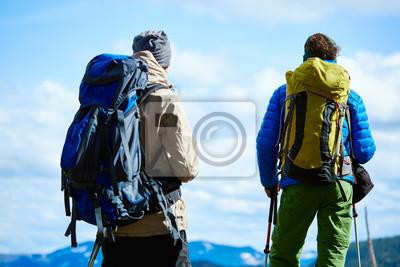 Zwei Wanderer mit Rucksack auf der Spur in den Karpaten Bergen im Winter. Wanderer steht auf dem bewölkten Himmel Hintergrund